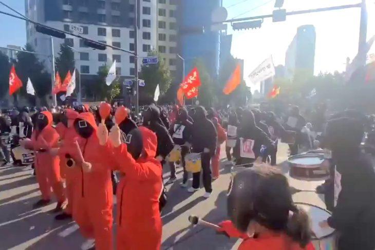 Squid Game című sorozat szereplőinek öltözött tüntetők Szöul utcáin október 20-án